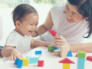 Asian mom and girl kid playing with blocks. Vintage effects and