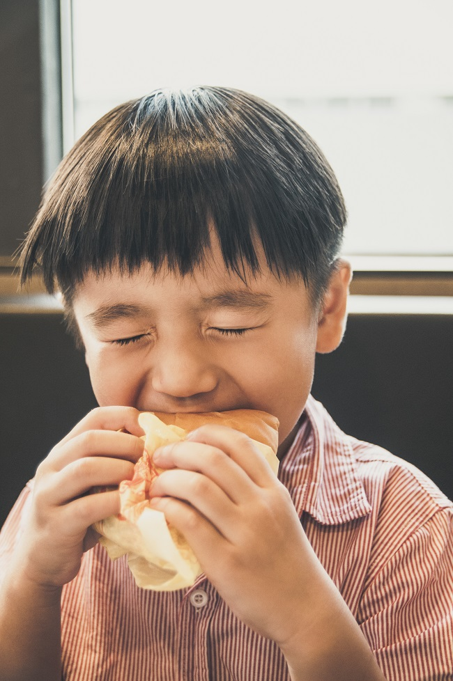 Portrsit of a young Asian boy eating yummy burger with oozing facial expression